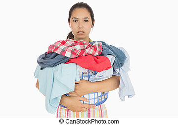 Frowning woman holding basket which is full of dirty laundry...