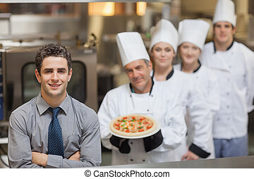 Waiter standing in front of Chefs holding a pizza