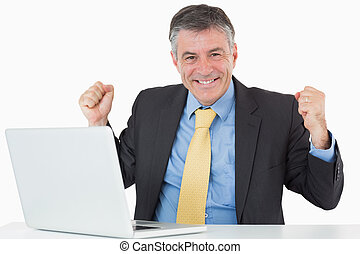 Successful man sitting at his desk with laptop - Successful...