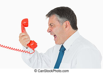 Angry businessman yelling at phone - Angru businessman...