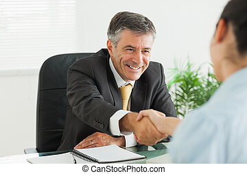 Man shaking a woman's hand in an office