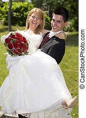 wedding - young groom holding a bride outside portrait