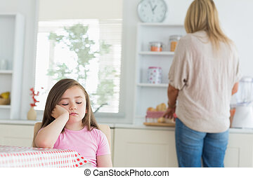 Child falling asleep at kitchen table with mother working on...