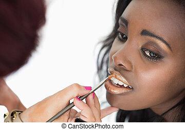makeup artist applying golden lip gloss