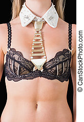 Close-up of a golden tie-necklace over bra