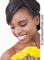 Woman smiling while holding yellow flowers - Woman is...