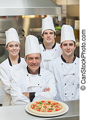 Smiling group of Chefs with a pizza on the counter