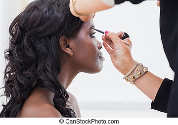 Woman sitting while getting eyebrows done - Woman sitting...
