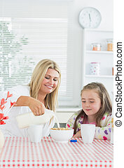 Mother pouring milk into cereal bowl for daughter at...