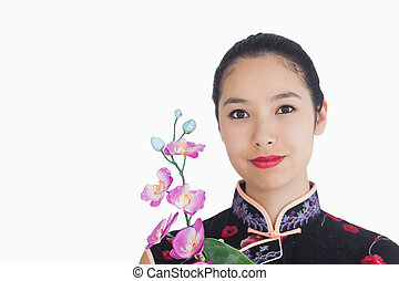 Woman holding an orchid while smiling and wearing a kimono