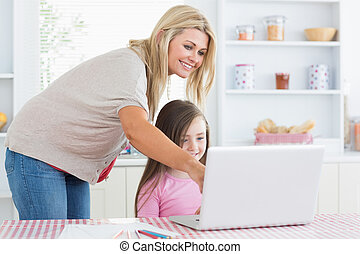 Mother pointing at laptop with daughter - Moher pointing at...