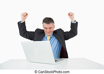 Man being victorious at his desk with his laptop on white...