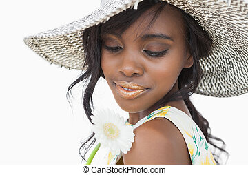 Woman wearing summer hat and holding white flower against...
