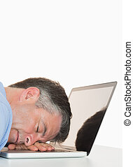 Exhausted man sleeping on his laptop on his desk