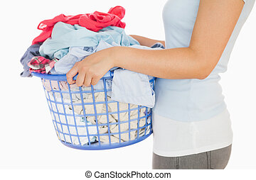 Woman holding a basket overflowing of laundry - Woman...