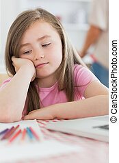 Girl sitting looking bored with paper and colouring pencils...