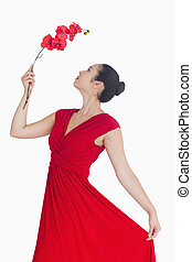 Woman posing with orchid in red dress
