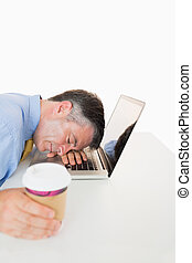 Tired man sleeping on his laptop while holding coffee -...