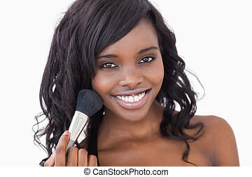 Woman smiling while holding a makeup brush against white...