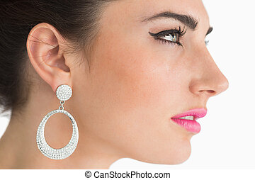 Woman wearing earrings in sixties makeup on white background
