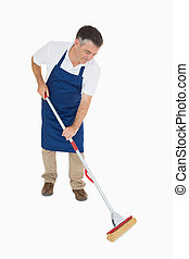 Man mopping the floor - Man in blue apron mopping the floor