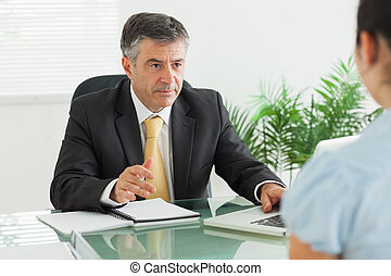 Businessman having a meeting with a woman in his office