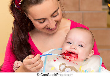 mother with her snotty son - Mother is spoon feeding her...