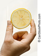 Lemon wedge - Woman hand holding up a wedge of lemon,...