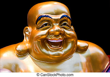 Smiling Buddha - The gold colored face of a statue of a...
