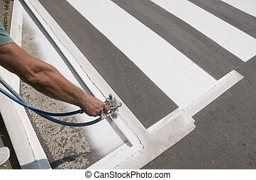 Crosswalk repairing - Hand spraying of pedestrian crosswalk...