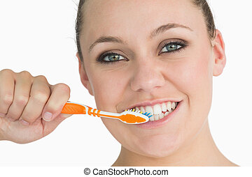 Woman washing her teeth in the white background
