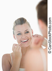 Woman using dental floss in front of mirror in the white...