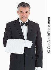 Smiling waiter holding a towel - Smiling and standing waiter...