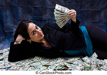Rich woman - Rich business woman waving money and laying...