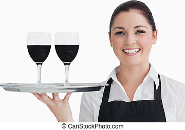 Happy waitress holding two glass of wine on a silver tray in...