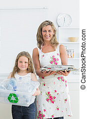 Smiling mother and daughter standing in the kitchen with waste for recycling