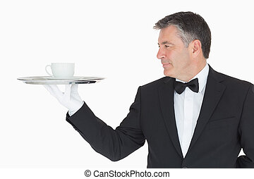 Waiter holding silver tray with cup - Waiter in suit holding...