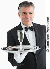 Smiling man serving champagne on tray - Smiling man serving...