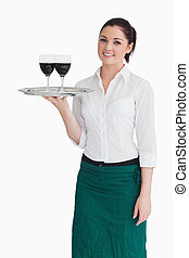 Woman holding tray with glasses of wine - Smiling woman...