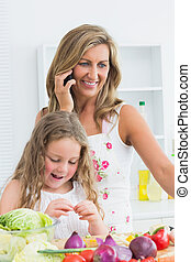 Mother phoning while her daughter working with vegetable -...