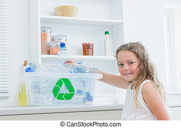 Girl sorting plastics into crates - Smiling girl sorting...