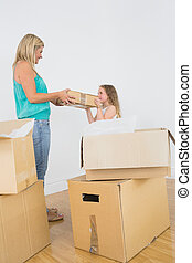 Smiling mother and daughter holding moving box in empty...