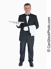 Smiling waiter holding out tray - Smiling waiter holding out...