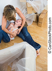Mother tickling her daughter on the floor