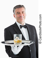 Man serving whiskey on toy - Smiling man serving whiskey on...