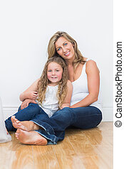 Mother and daughter sitting on the floor - Happy mother and...