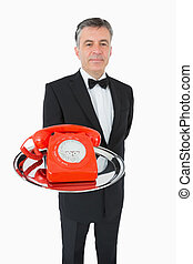 Well-dressed waiter holding a phone on a silver tray -...