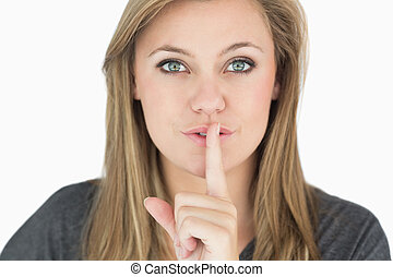 Blond woman putting finger on mouth in the white background