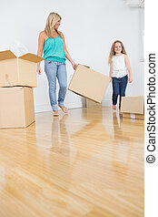 Mother and daughter holding a moving box together in empty...