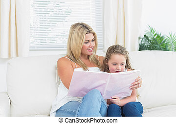 Mother and daughter reading a book - Smiling mother and...